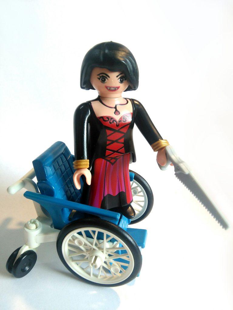 Femme fatale playmobil, debout sur un fauteuil roulant, une scie à la main, sourire carnassier